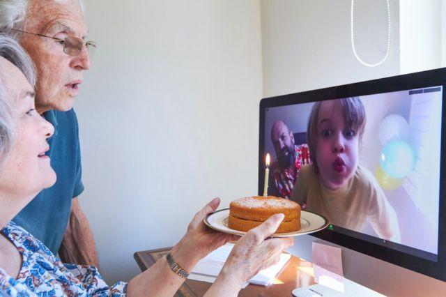 Abuelos con pastel ven a su nieto