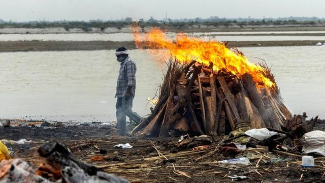 A man walks near incinerators where people have died from coronavirus disease, on the banks of the Ganges River in India