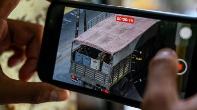 A person holds a mobile phone showing a video of soldiers looking out from a truck in Yangon on February 28, 2021, as security forces continue to crackdown on demonstrations by protesters against the military coup