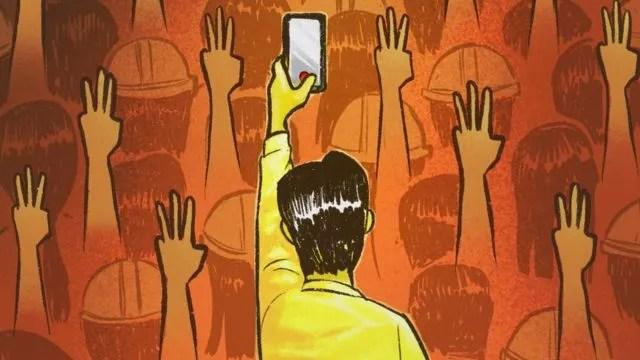 시위대 속에서 스마트폰을 들고 촬영 중인 남성