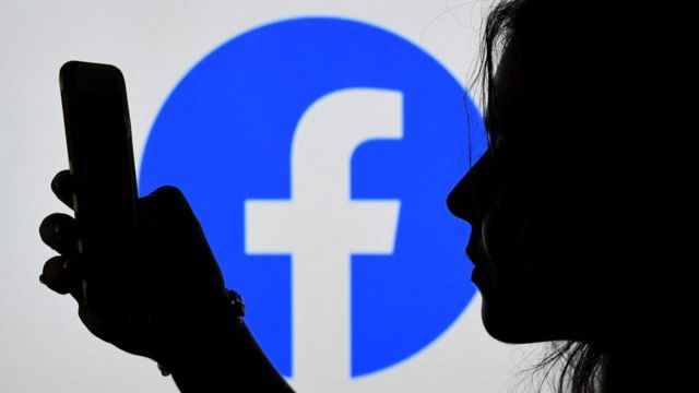 Shadow of woman looking at cell phone, with Facebook logo in background.