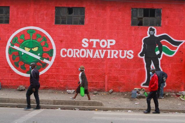 Pessoas no Quênia passam diante de um grafite em um muro retratando o coronavírus