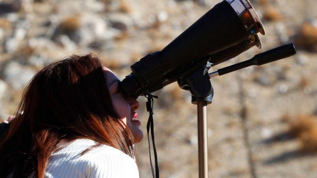 Mulher vendo o eclipse de 2019 no Chile