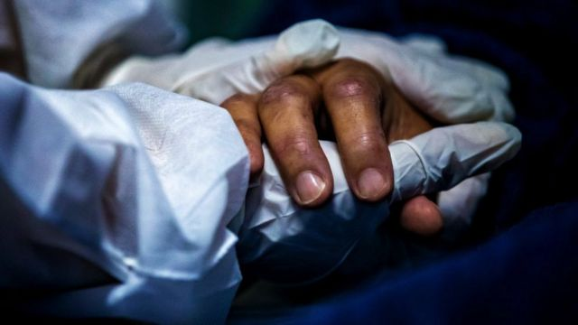 A health worker wearing personal protective equipment (PPE) holds a patient's hand on April 30, 2021 at a hospital in Maricá, Brazil
