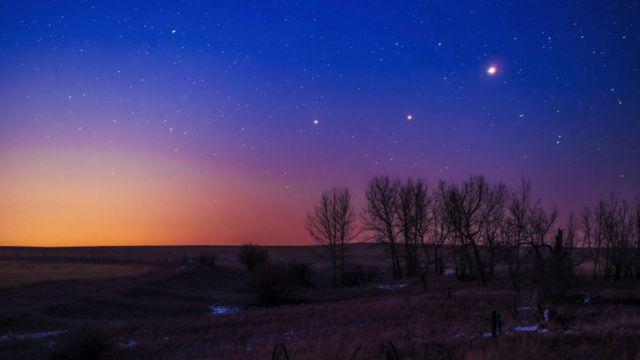 Campo com algumas árvores sob céu ao amanhecer, repleto de estrelas e pontos iluminados