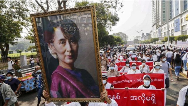 Protesters hold a portrait of San Suu Kyi