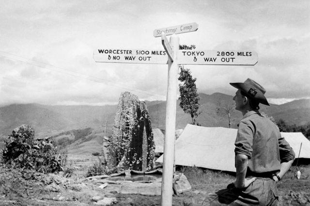 El ejército británico en Birmania 1944: un miembro de Worcestershire Yeomanry ve una divertida señal de tráfico junto a un antiguo monolito en el 'Campamento Stonehenge' en la carretera de Imphal a Kohima.