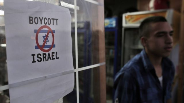 A Palestinian boy leaves a store that had erected a poster calling people to boycott Israel in east Jerusalem