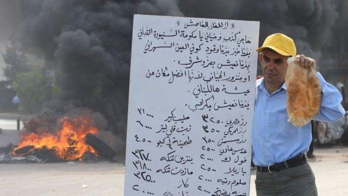 Un homme tient une miche de pain et une pancarte lors des manifestations contre le prix des denrées alimentaires au Liban, le 7 mai 2008.