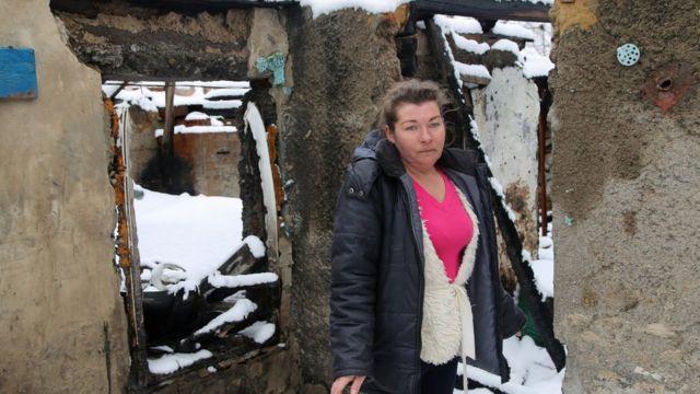Женщина стоит у своего дома, разрушенного снарядом, недалеко от Донецка.