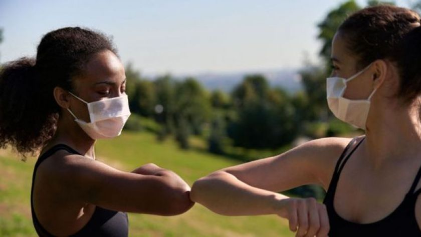 Two young women in masks greet each other with their elbows