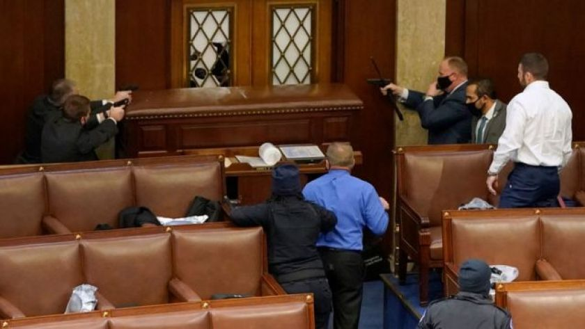 Capitol cops point guns at a protester from within the Senate