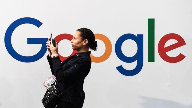 Mujer frente a un letrero de Google