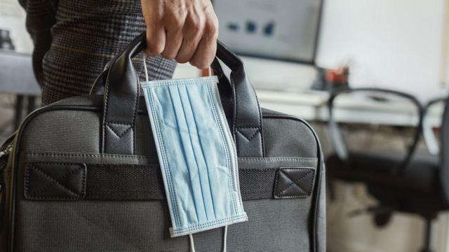 Un hombre lleva una mochila para laptop y una mascarilla.