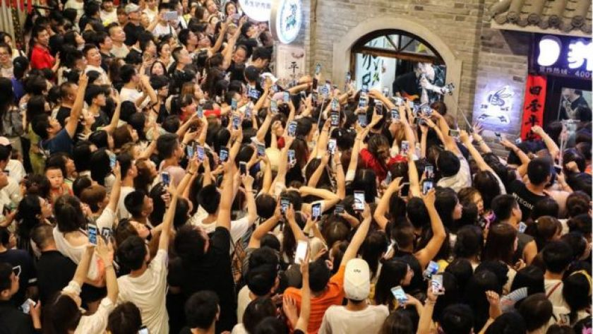 Fans record videos on their smartphones as boyband Modern Brothers perform during a live webcast on Andong Old Street on June 30, 2018 in Dandong, Liaoning Province, China.