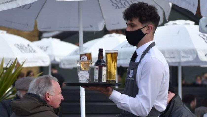 Masked waiter with drinks tray in a restaurant