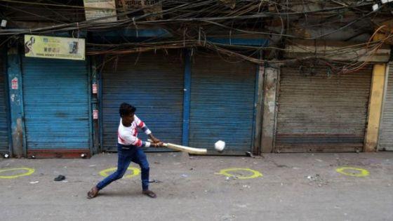Seorang anak laki-laki bermain kriket di pasar tertutup di pasar grosir Sadar Bazar selama penutupan akhir pekan yang diberlakukan oleh pemerintah negara bagian untuk mengekang lagi lonjakan kasus virus corona (Covid-19)