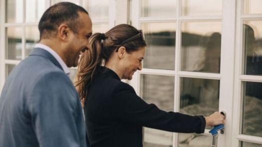 Mulher abrindo porta de casa ao lado de um homem