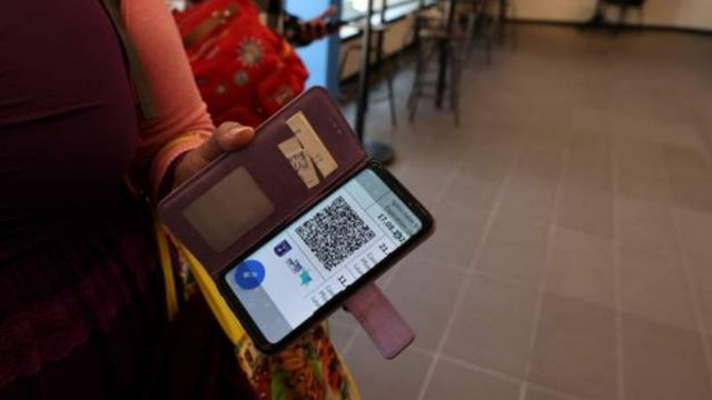 مواطنة تبرز تطبيق الجواز الأخضر على هاتفها قبل الدخول إلى مكان في إسرائيل
