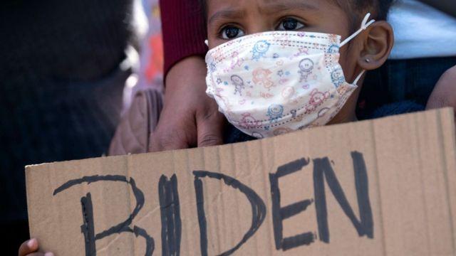 """Una niña sostiene un cartel que dice """"Biden"""" en una protesta en el puerto fronterizo de San Ysidro, en Tijuana, el 2 de marzo."""