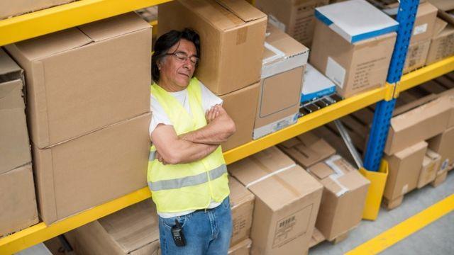 Un homme s'est endormi debout, il se repose sur une étagère pleine de cartons bruns.