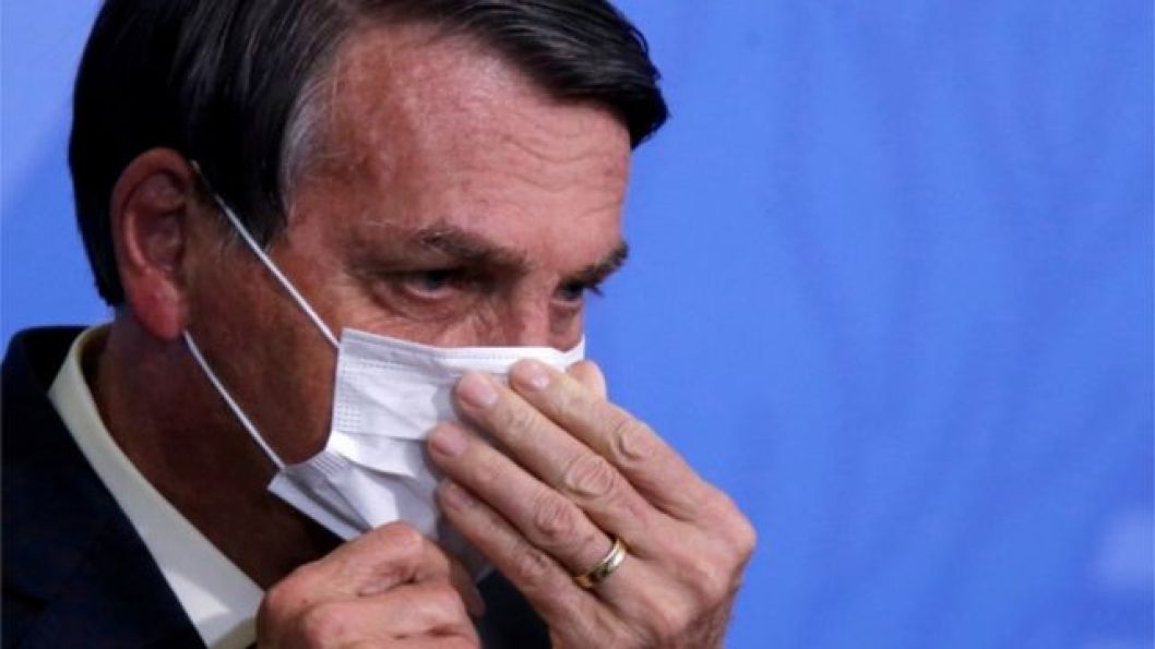 Jair Bolsonaro colocando máscara