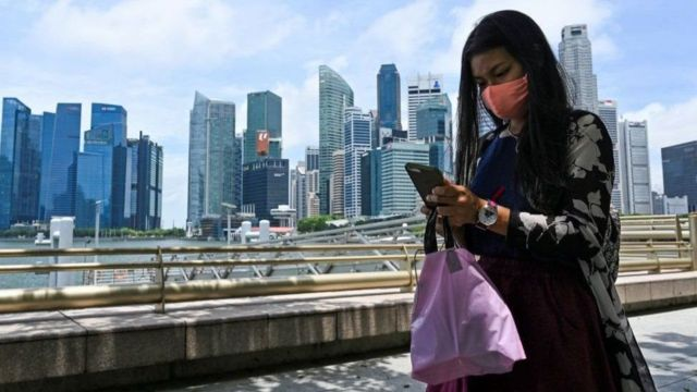 A woman checks her mobile phone in front of several skyscrapers