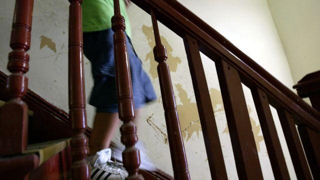 Criança descendo escadas em casa com paredes descascadas