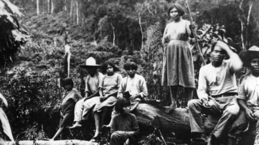 Indigenous people sitting on a piece of wood
