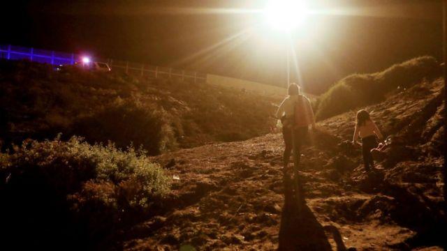 Una mujer camina en el lado estadounidense de la frontera con México junto a una niña.