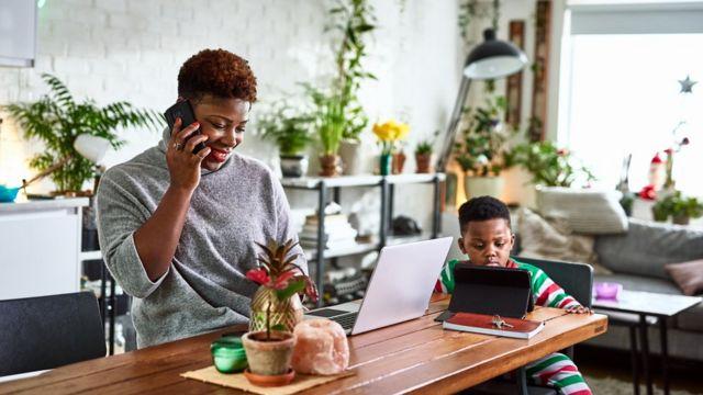 Mujer trabajando desde casa con su hijo.