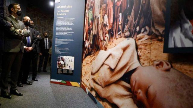 Le président français Emmanuel Macron (G) et le ministre français des Affaires européennes et étrangères Jean-Yves Le Drian s'arrêtent pour regarder des images lors de leur visite au Mémorial du génocide de Kigali, où sont enterrées quelque 250 000 victimes des massacres, à Kigali, le 27 mai 2021.