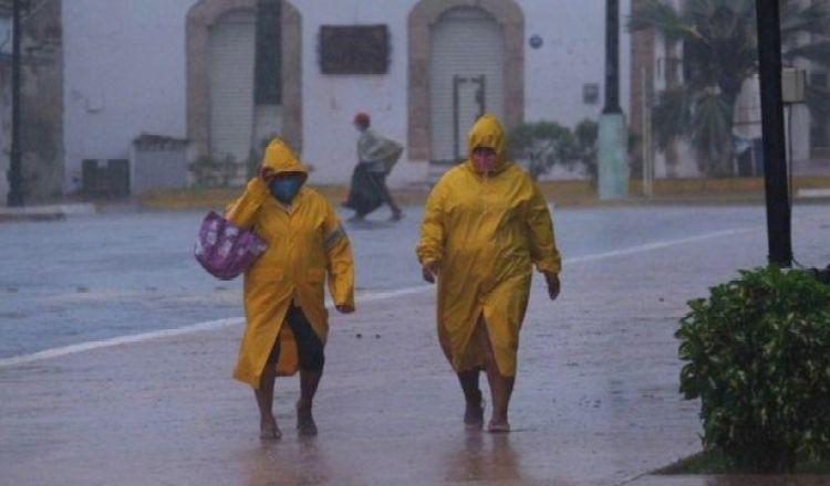 Personas cubiertas bajo la lluvia en Tizimín.