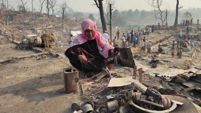A woman picks up what is left of her possessions from the fire