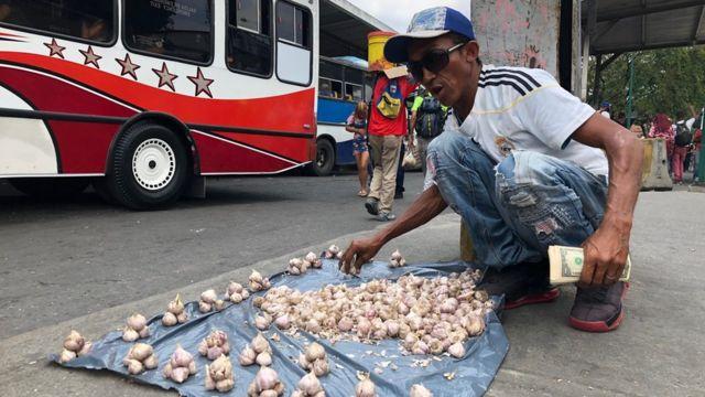 Homem vendendo alhos em uma rua de Caracas