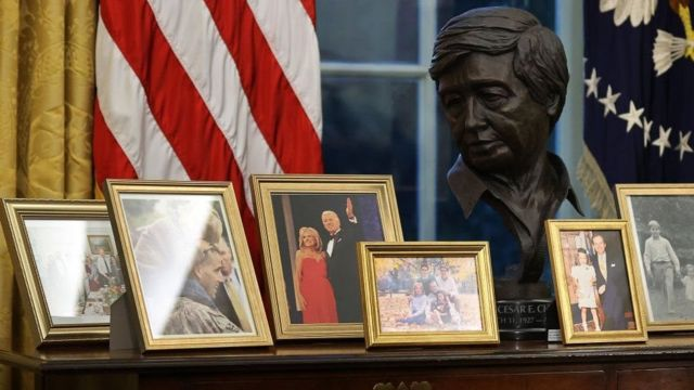 A bust of Cesar Chavez snaps beside photos of the Biden family