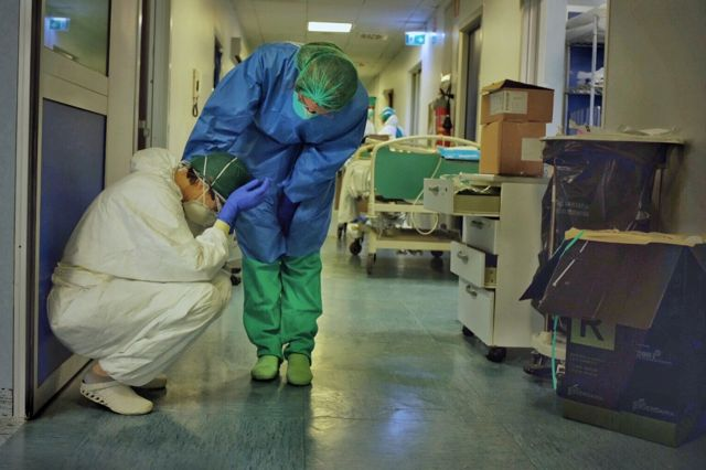 A hospital worker comforts his colleague in a corridor