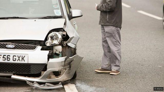 رجل يقف إلى جوار سيارة محطمة المقدمة