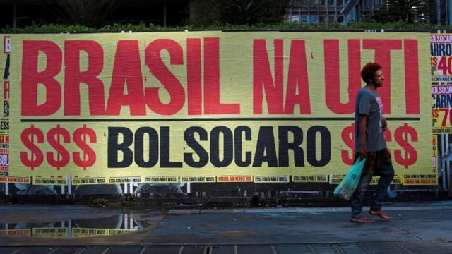 """Man walks barefoot in front of a banner that says """"Brazil in the ICU, Bolsocaro"""" in São Paulo, Brazil, March 8, 2021"""