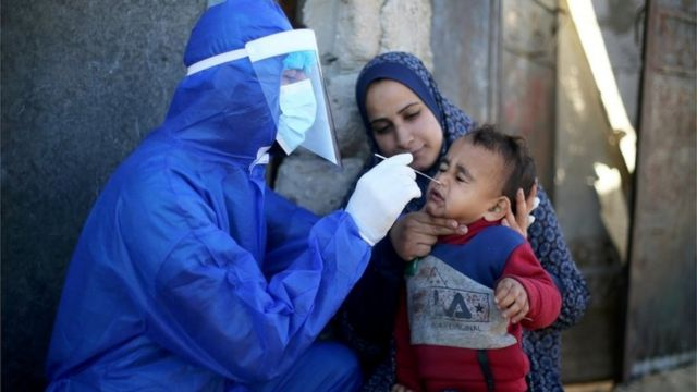 A Palestinian medical official conducts a Corona virus swab for a child