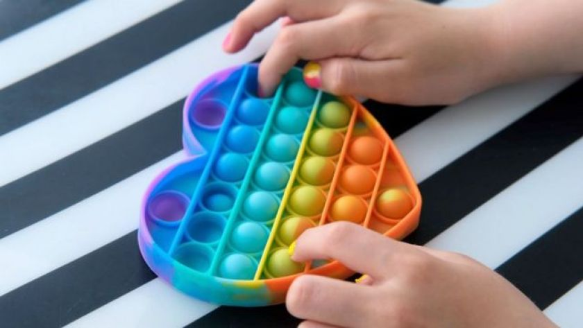 Child's hand playing with a rubber briqnued with several balls to squeeze