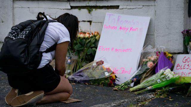 鲜花和招牌上点缀着金水疗中心(Gold Spa),活动家在星期二晚上的枪击事件后示威反对暴力侵害妇女和亚洲人的行为,该事件于2021年3月18日在佐治亚州亚特兰大被枪杀。