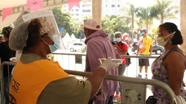 Debaixo de toldo, mulher com itens de proteção contra o coronavírus entrega uma marmita para pessoa em fila