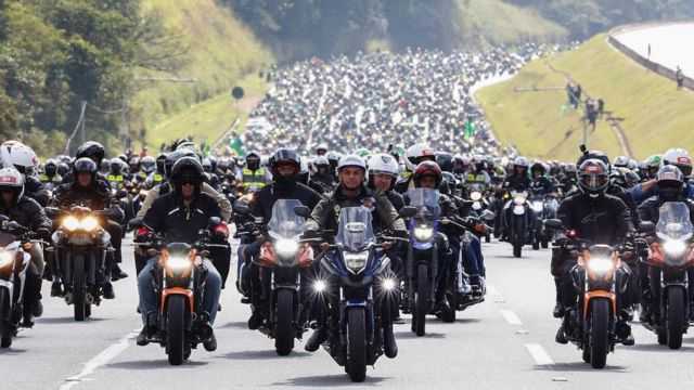 A mimeographed photo made available by the Brazilian Presidency that shows Brazilian President Jair Bolsonaro (C) on a motorcycle tour with his supporters, in Sao Paulo, Brazil on June 12, 2021