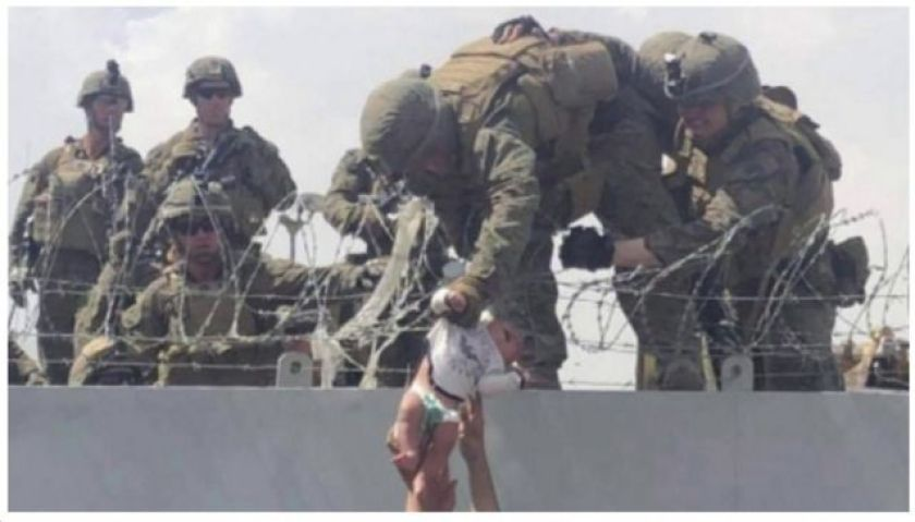 Soldiers hold baby being passed over fence