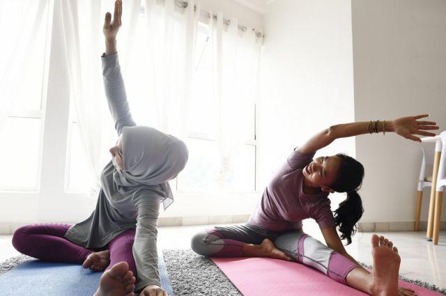امرأة وابنتها تمارسان بعض اليوغا في المنزل