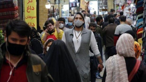 المارة في أحد شوارع طهران يرتدون الكمامات
