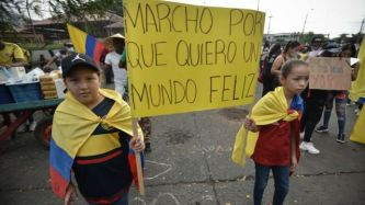 """Niñas marchando en una protesta en Colombia sosteniendo un cartel con la leyenda: """"Marcho porque quiero un mundo feliz""""."""
