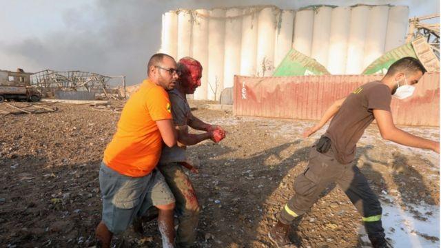 Dos hombres ayudan a otro herido a caminar tras la explosión en Beirut.