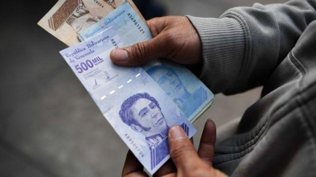 Una persona sostiene unos billetes de 500.000 bolívares.